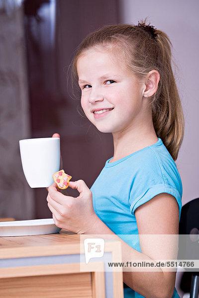 11 Jähriges Mädchen Mit Tasse Sitzt Am Tisch Ibxvth02111198