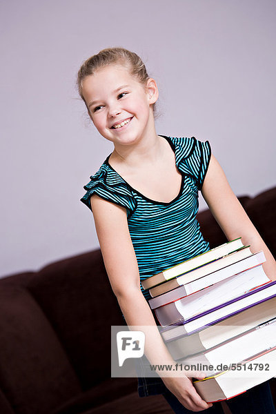 8-jähriges Mädchen mit einem Stapel Bücher