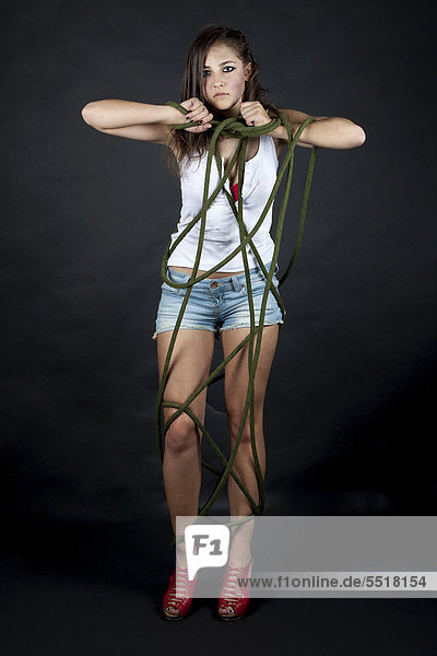 Young woman, dirty and tied up with rope
