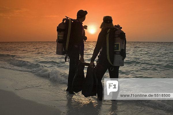 Taucher beobachten am Strand den Sonnenuntergang  vor dem Nachttauchen  Malediven  Indischer  Ozean  Asien
