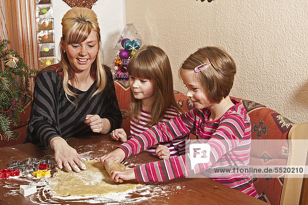Mother with children  twin girls baking biscuits