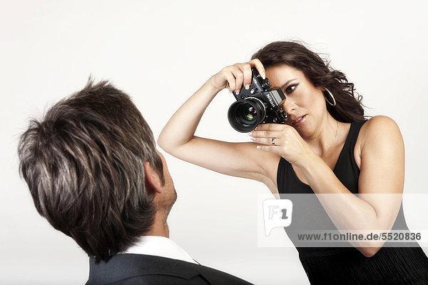 Junge Frau fotografiert einen Mann mit einer alten,  analogen Nikon Kamera
