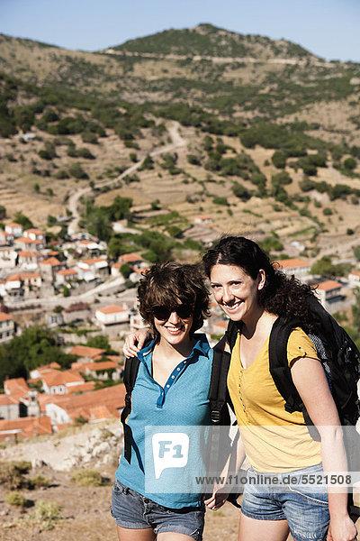 Frauen lächeln zusammen auf dem Hügel