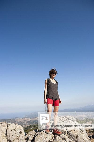 Wanderer auf Felsen am Berg stehend
