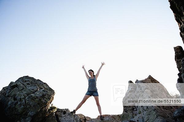 Frau jubelt auf Felsen