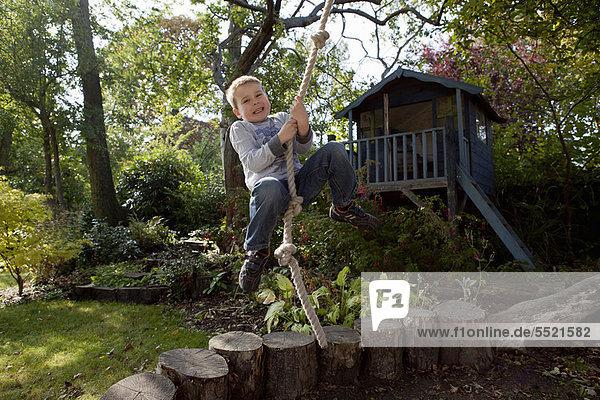 schaukeln  schaukelnd  schaukelt  schwingen  schwingt schwingend  Junge - Person  Seil  Tau  Garten  Hinterhof  spielen  Schaukel