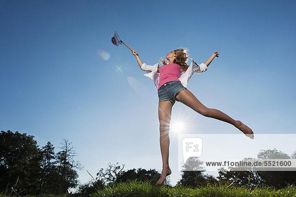 Frau mit Schmetterlingsnetz im Freien