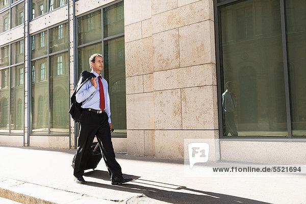 Geschäftsmann rollt Gepäck ins Freie