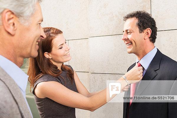 Geschäftsfrau beim Anpassen der Krawatte eines Kollegen