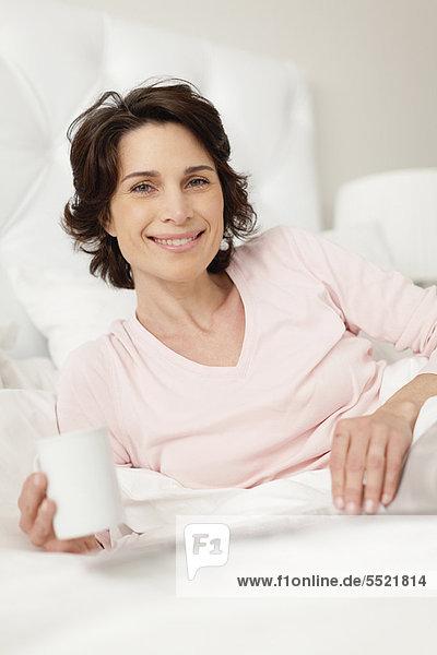 Frau  lächeln  Bett  Zeitung  vorlesen