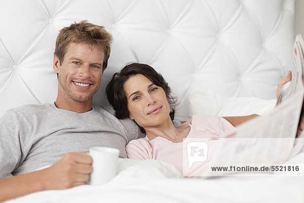 Lächelndes Paar liest Zeitung im Bett