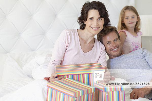 Familie mit Muttergeschenken im Bett