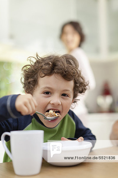 Junge beim Frühstücken in der Küche