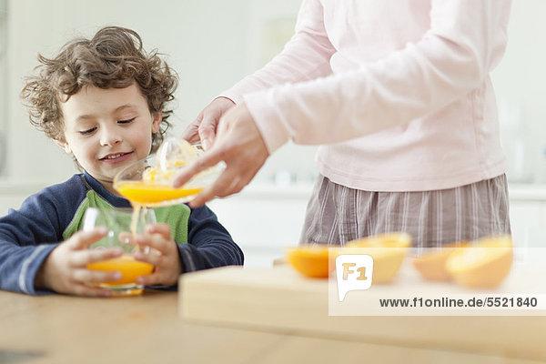 Mutter gießt Orangensaft für Sohn