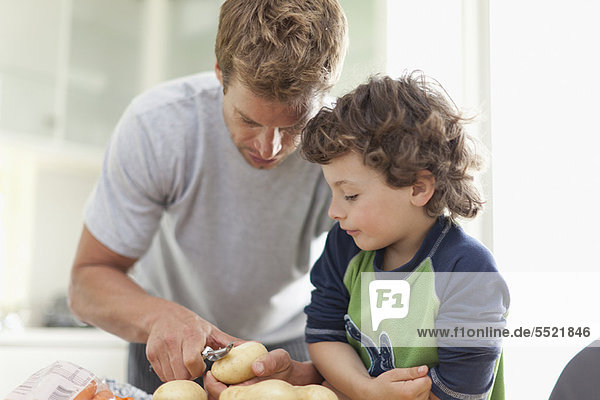 Vater hilft Sohn Kartoffeln schälen