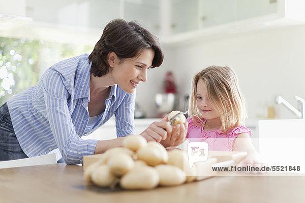 Mutter hilft Tochter beim Schälen von Kartoffeln