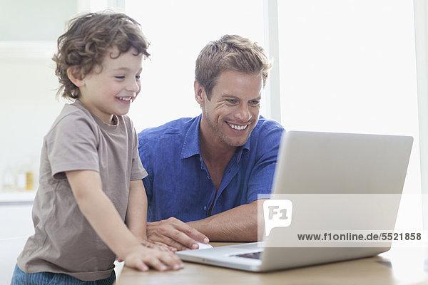 Vater und Sohn nutzen gemeinsam den Laptop
