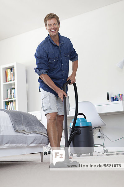 Smiling man vacuuming living room