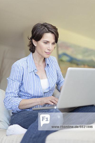 Lächelnde Frau mit Laptop auf der Couch
