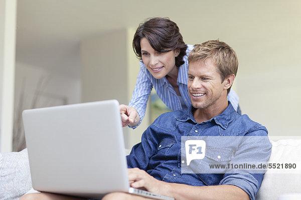 Paar mit Laptop zusammen auf der Couch