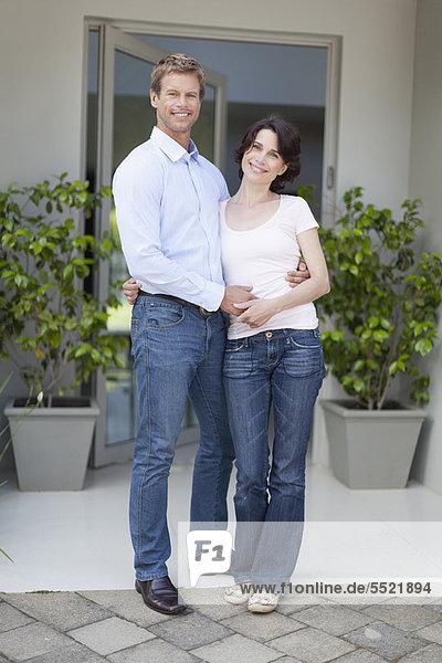 Paar lächelt vor der Haustür
