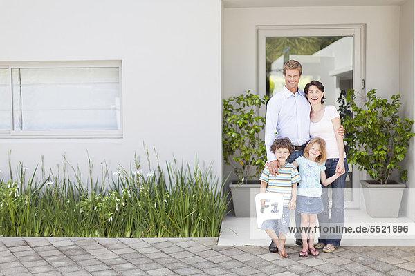 Familie lächelt vor der Haustür