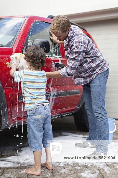 Vater und Sohn waschen gemeinsam Auto