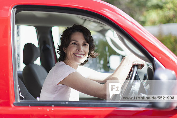Frau lächelt im Fahrersitz des Autos