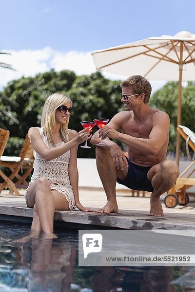 Couple toasting each other by pool