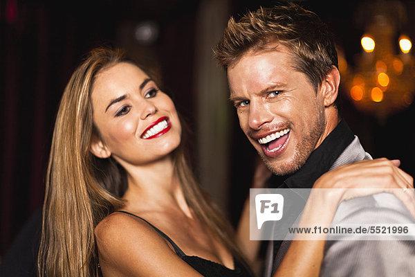 Lächelndes Paar tanzt im Club