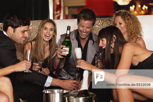 Friends drinking champagne in club