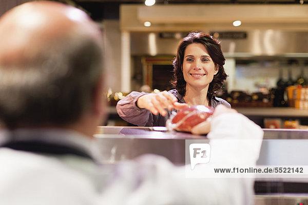 Frau kauft Fleisch vom Metzger