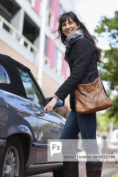 Frau entriegelt Auto auf der Stadtstraße