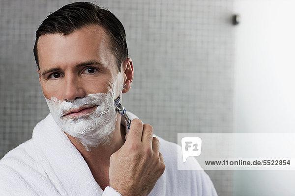 Man shaving in bathroom