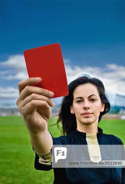 Frau mit roter Karte auf dem Fußballplatz
