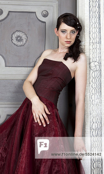 Junge Frau mit rotem Kleid steht an Tür  Portrait