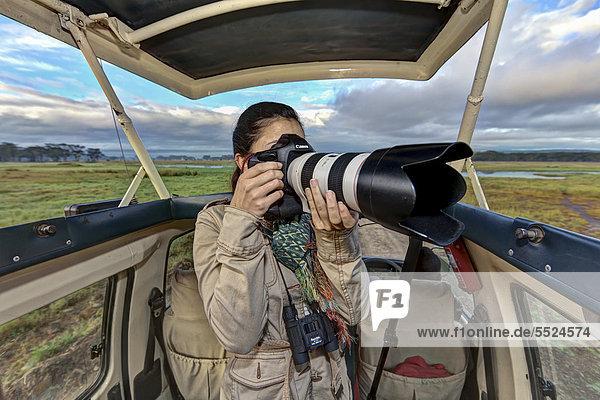 Junge Fotografin macht Bilder aus einem Safaribus heraus  Lake Nakuru Nationalpark  Kenia  Ostafrika  Afrika  ÖffentlicherGrund