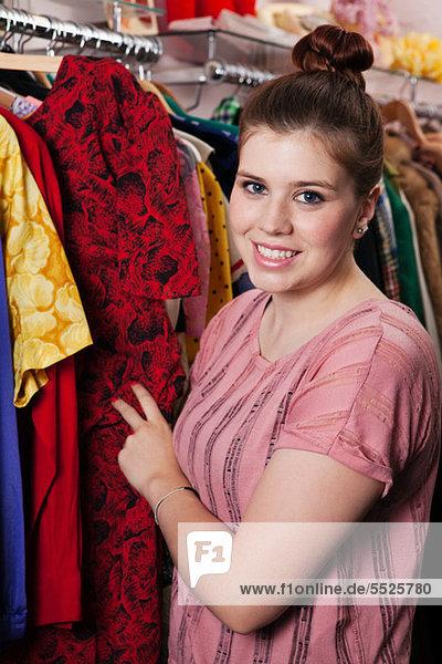 Junge Frau beim Anblick von Kleidern im Bekleidungsgeschäft  Porträt