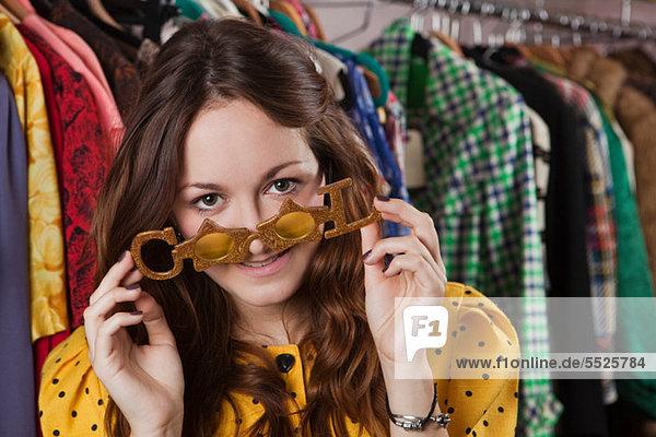 Junge Frau versucht auf Spaßbrille in Kleidung Shop  Lächeln