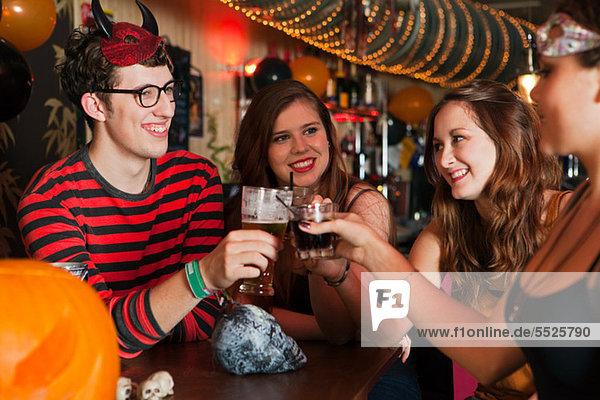 Junge Freunde toasten Getränke in der Bar