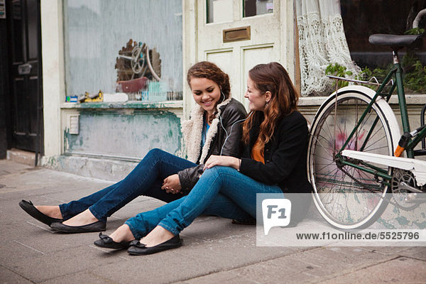 Zwei junge Frauen sitzen auf dem Bürgersteig vor dem Café.