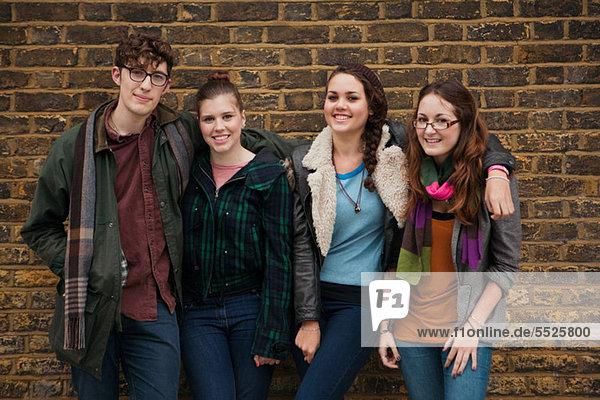 Vier junge Freunde gegen Wand  Lächeln