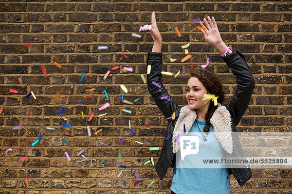 Junge Frau wirft buntes Konfetti gegen die Ziegelwand