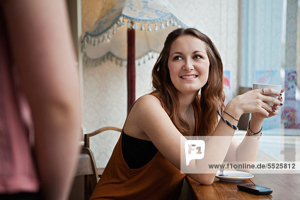 Young woman in cafe smiling at friend