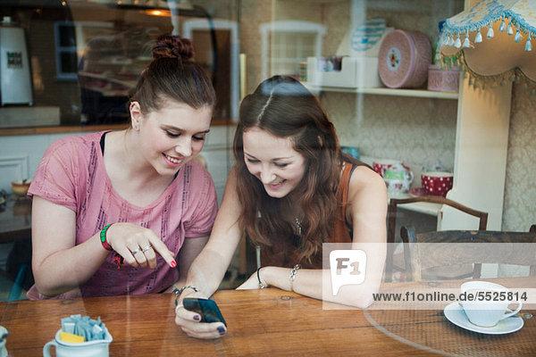 Junge Frauen im Cafe beim Blick aufs Handy