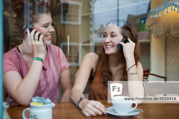 Junge Frauen im Café auf Handys