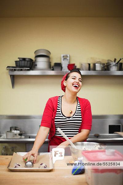 Junger Bäcker lacht bei der Zubereitung des Essens
