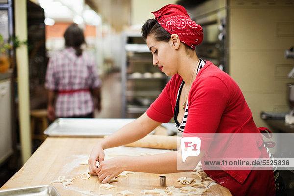 Junger Bäcker bei der Zubereitung von Speisen in der Küche