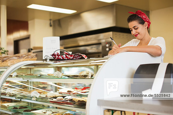Junge Frau arbeitet an der Theke der Bäckerei