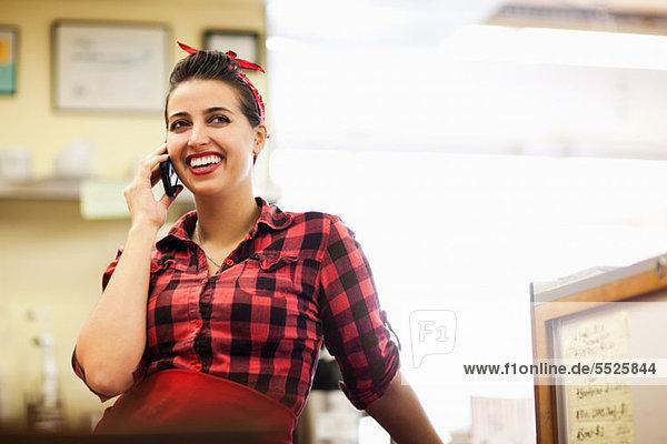 Junge Frau einen Anruf in der Bäckerei
